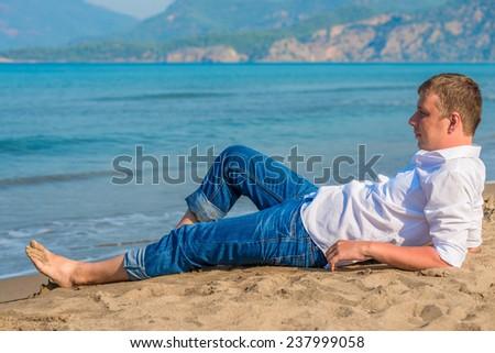 male businessman lying on the beach near the sea - stock photo