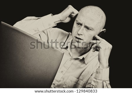 male businessman on phone looking into laptop frustrated
