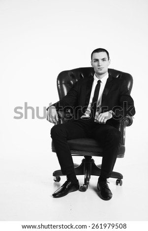 Male businessman sitting on a green leather chair on a white background. The man exudes self-confidence, success, wealth. Money, success, prosperity.