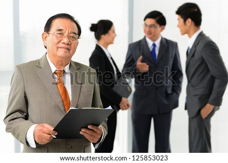 Male businessman standing and looking at camera