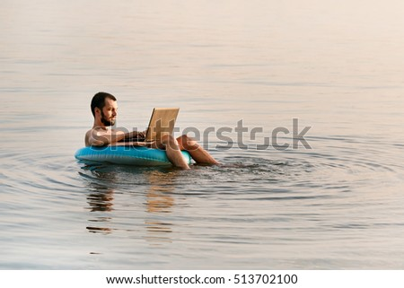 Male businessman with a laptop on inflatable ring in the water