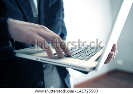Male Businessman Working While Standing on the Laptop in Office Area. Computers Technology Photo Collection. - stock photo