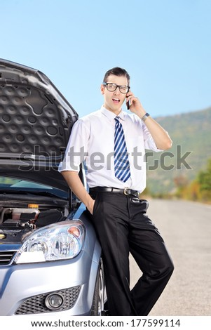 Male businessperson talking on phone next to a car with its bonnet open on an open road. - stock photo