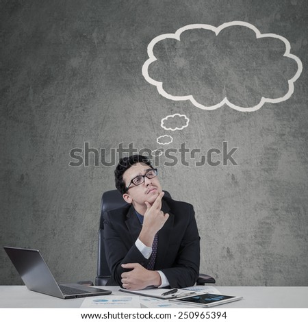 Male businessperson working on desk while looking at empty cloud tag for copy space - stock photo