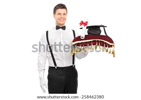 Male butler holding a diploma and a mortarboard on a red pillow isolated on white background - stock photo