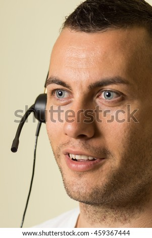 Male call center worker with headset. High resolution image depicting call center or helpline worker.