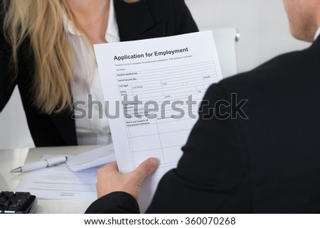 Male candidate holding application form in front of interviewer in office