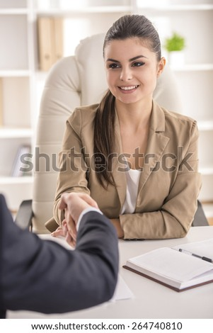 Male candidate shaking hands with businesswoman at desk in office - stock photo
