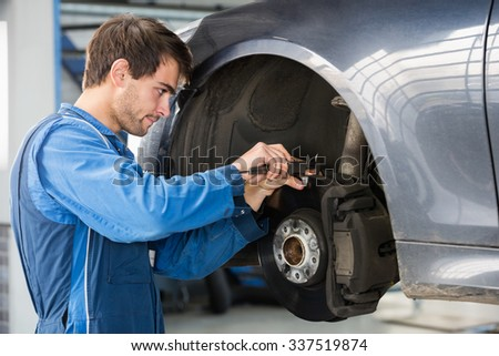 Male car mechanic examining brake disc with caliper in garage - stock photo