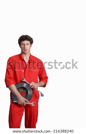Male car mechanic, in red overalls, holding vehicle part and wrenches, smiling, portrait, cut out - stock photo