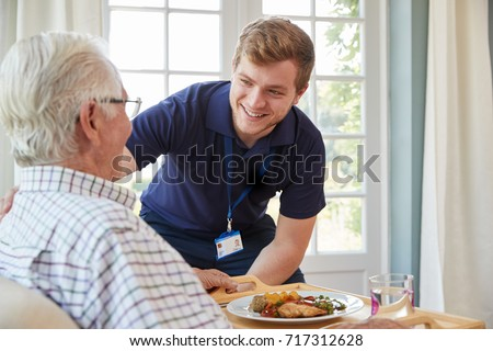 Male care worker serving dinner to a senior man at his home