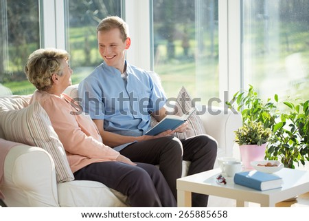 Male carer spending time with elder woman - stock photo