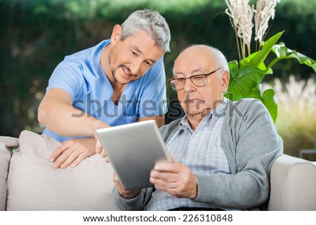 Male caretaker assisting senior man in using digital tablet at nursing home porch - stock photo