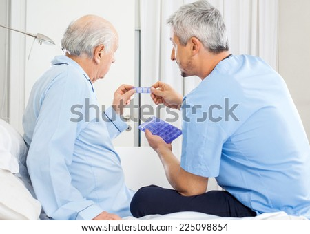 Male caretaker guiding prescription to senior man in bedroom at nursing home - stock photo