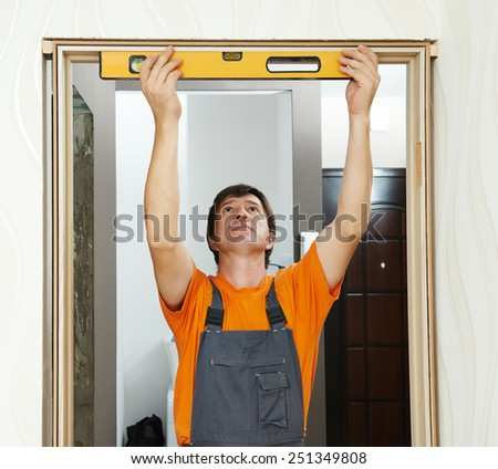 Male carpenter at interior wood door installation working with level - stock photo