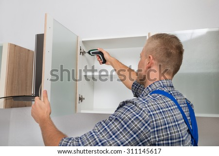 Male Carpenter Drilling In Cabinet With Electric Cordless Drill