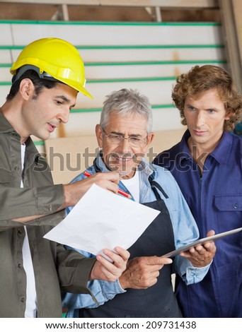 Male carpenters discussing over document in workshop - stock photo