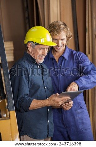 Male carpenters using tablet computer together in workshop - stock photo
