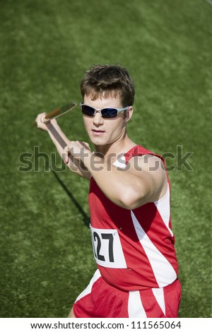 Male Caucasian athlete throwing javelin - stock photo