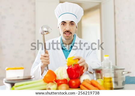 Male caucasian cook in uniform cooking with ladle in kitchen - stock photo