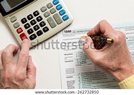 Male caucasian hand holding pen above USA tax form 1040 for year 2014  and calculator illustrating completion of tax forms for the IRS - stock photo