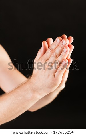 Male Caucasian hand praying in front of black background