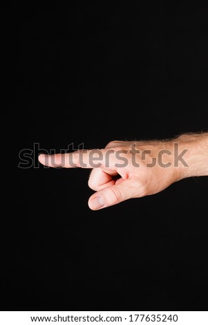 Male Caucasian hand showing blaming finger in front of black background