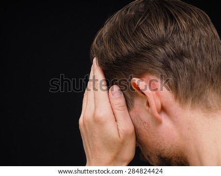 Male caucasian person covering face with one hand isolated towards black - stock photo
