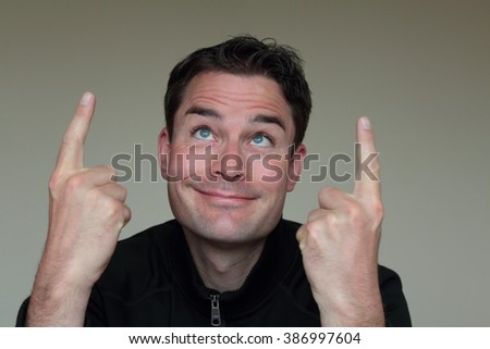 Male caucasian pointing up with both hands. Man with dark hair holding both hands up and pointing direction up with his first fingers. - stock photo