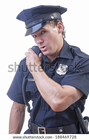 Male Caucasian police officer in blue cop uniform talks on his radio receiver on white background - stock photo