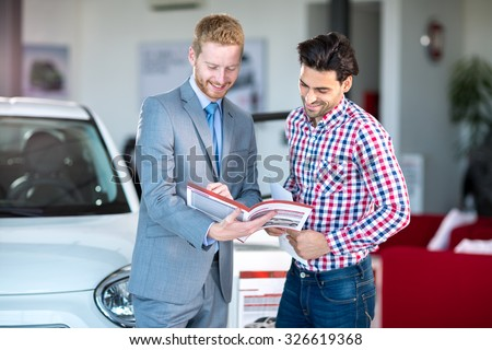 Male Caucasian salesman and male client at the car dealership saloon indoors - stock photo