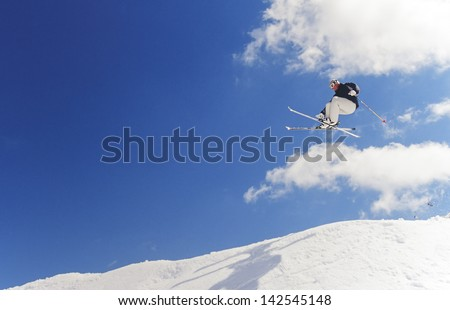Male caucasian skier jumping high in snowpark with blue sky background and copy space