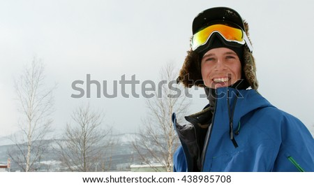 Male Caucasian Skier Profile Portrait Holding Skis Wearing Goggles Hat, Jacket, Winter Gear. Looking at Camera Smiling Snowy Landscape Background. - stock photo