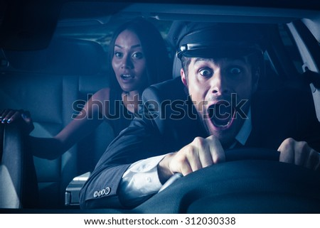 Male chauffeur with woman on back seat gets into car crash and makes ridiculous face - stock photo