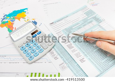 Male checking 1040 USA Tax Form with silver ball pen - studio shot - stock photo