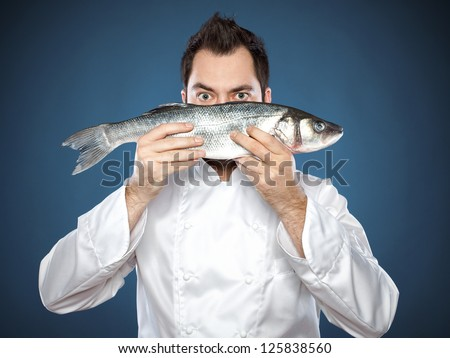 Male chef hidding behind the sea bass fish