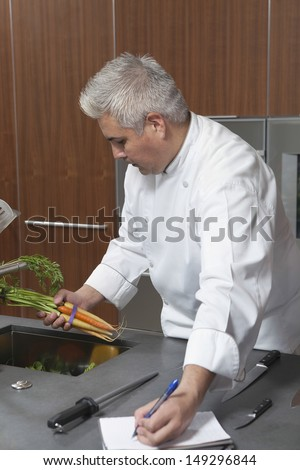 Male chef holding carrots and writing in notebook at commercial kitchen - stock photo