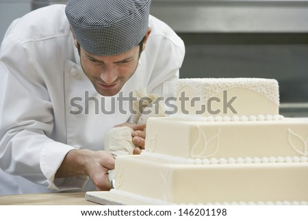 Male chef icing wedding cake in kitchen - stock photo