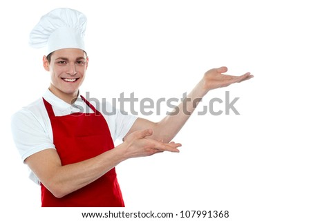 Male chef in red uniform presenting copy space isolated over white