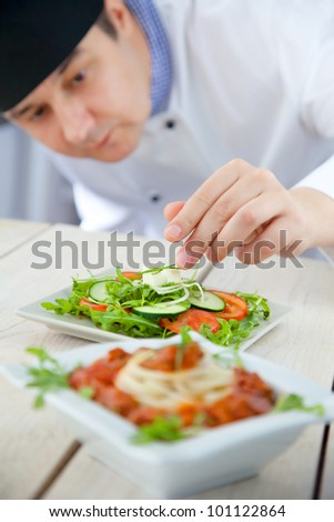 Male chef in restaurant kitchen is garnishing and preparing pasta dish - stock photo