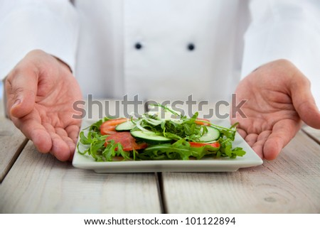 Male chef in restaurant kitchen is garnishing and preparing pasta dish - stock photo