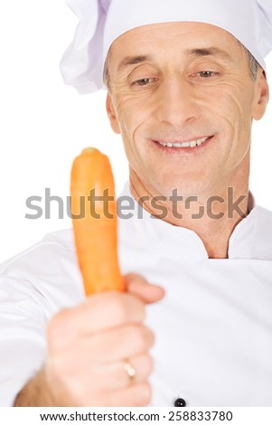 Male chef in uniform holding a carrot - stock photo