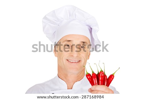 Male chef in uniform holding chilli peppers - stock photo