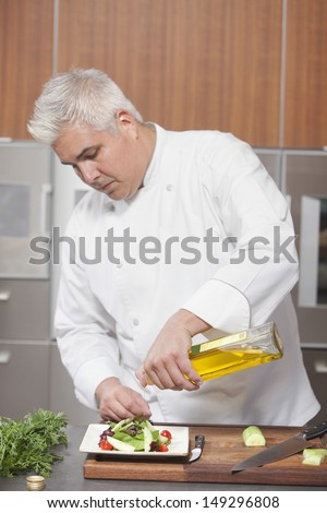 Male chef pouring olive oil over freshly prepared salad in commercial kitchen - stock photo
