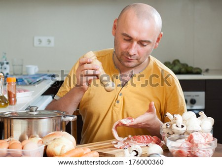 male chef prepares a dish of meat - stock photo