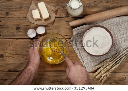 Male chef prepares on rustic kitchen. Ingredients for bakery products. Top view - stock photo