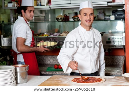 Male chef preparing the pizza base with sauce - stock photo