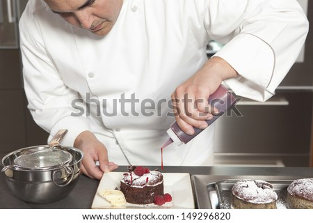 Male chef puts finishing touches on chocolate cake at counter of commercial kitchen - stock photo