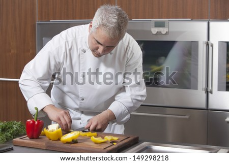 Male chef slicing bell pepper in commercial kitchen - stock photo