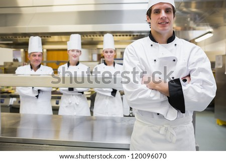 Male chef standing in kitchen with team behind him - stock photo